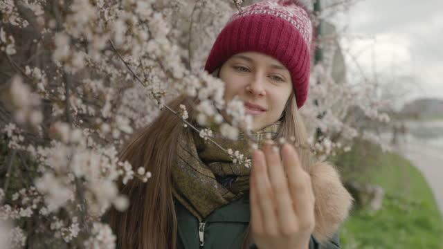 Teenage girl enjoying spring flowers on hawthorn bush.