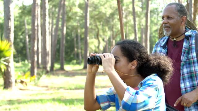 十代の少女, 祖父ハイキング, 森を探索 - バードウォッチング点の映像素材/bロール