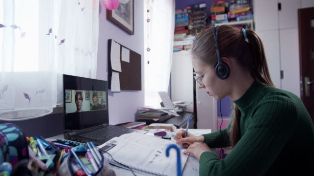 vídeos de stock e filmes b-roll de teenage girl having online lesson in her room. - isolado
