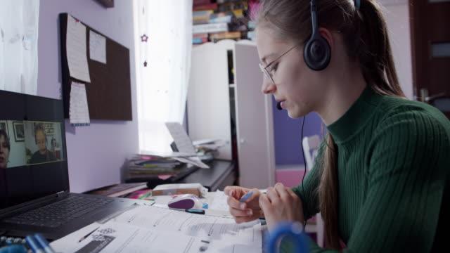 stockvideo's en b-roll-footage met tiener die online les in haar ruimte heeft. - online leren