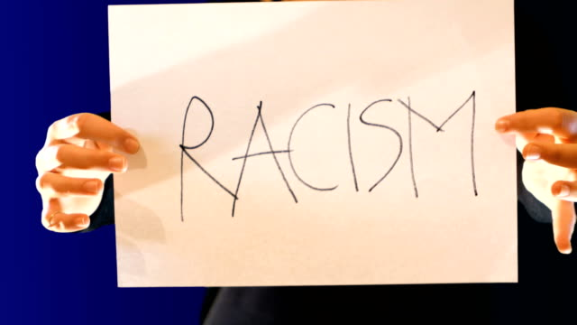 teenage girl holds a paper sign in her hand, with the word racism. Crumple the sign to protest, ideal footage to raise racism problems