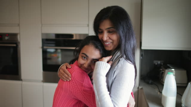 A Teenage Girl Hugging her Mother A young girl is standing in the kitchen with her mother, giving her a loving hug. indian family stock videos & royalty-free footage