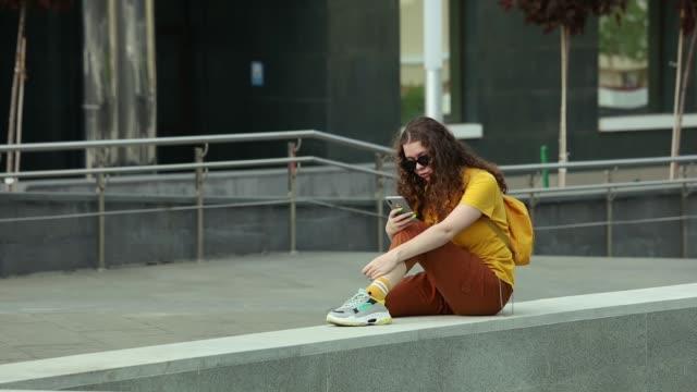 tonårsflicka i en gul t-shirt sitter på en hög trottoarkant och läser meddelanden på sin smartphone - endast en tonårsflicka bildbanksvideor och videomaterial från bakom kulisserna