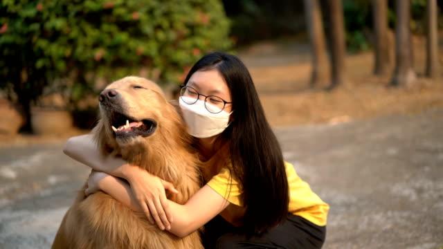 Video Teenage Girl in air pollution mask hug Golden Retriever