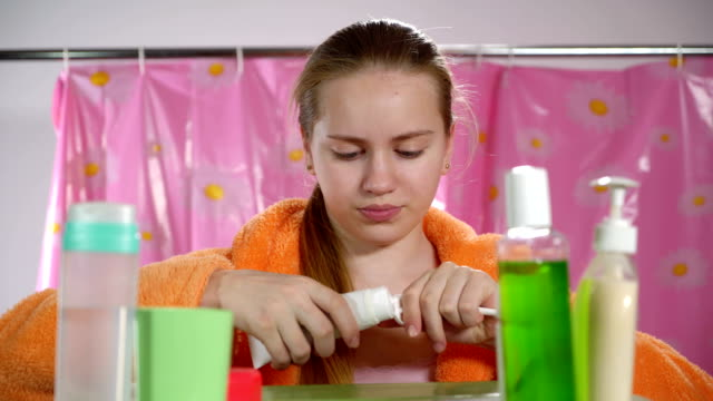 Teenage girl in bathrobe brushing her teeth in bathroom looking in the mirror video