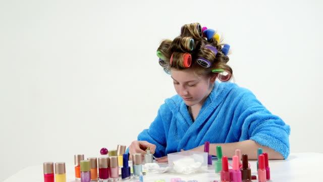 teenager-mädchen in lockenwickler mit nagellack sammlung malerei nägel zu hause - maniküre stock-videos und b-roll-filmmaterial