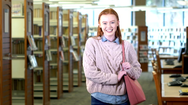 teenager-mädchen in high-school-bibliothek - rotes haar stock-videos und b-roll-filmmaterial