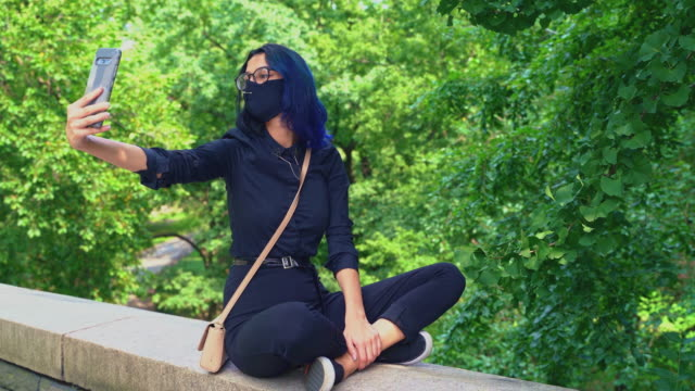 Teenage girl is sitting on the stone fence of Central Park, Manhattan, and taking selfies with a smartphone. A 17-years-old teenage girl wearing protective mask in Central Park, Manhattan, NY. 4K UHD video footage. blue hair stock videos & royalty-free footage