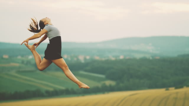 MS Teenage girl jumping for joy in rural field Teenage girl jumping for joy in rural field. Slow Motion. full length stock videos & royalty-free footage