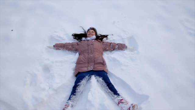 vídeos de stock e filmes b-roll de teenage girl laying on snow and making snow-angel - family christmas