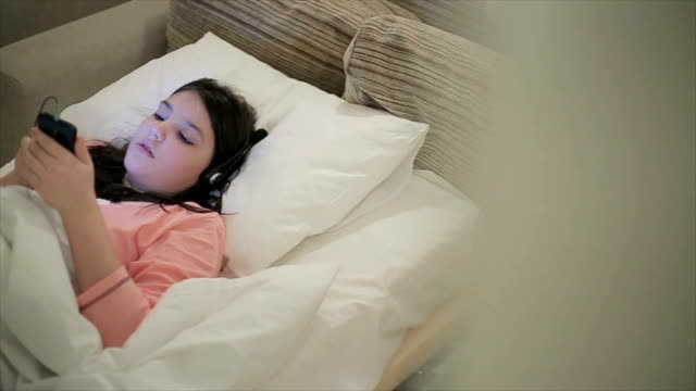 Teenage girl listen music on headphones in bed at night video
