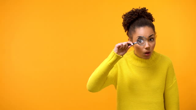 Teenage girl looking in magnifying glass, shocked and surprised by information Teenage girl looking in magnifying glass, shocked and surprised by information magnifying glass stock videos & royalty-free footage