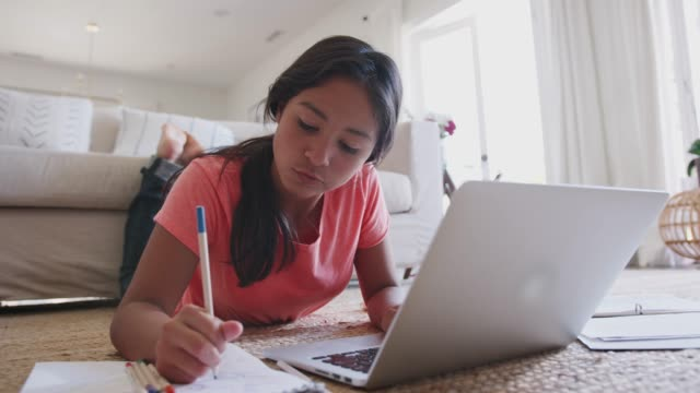 Teenage girl lying on the floor doing her homework using a laptop computer, low angle, close up