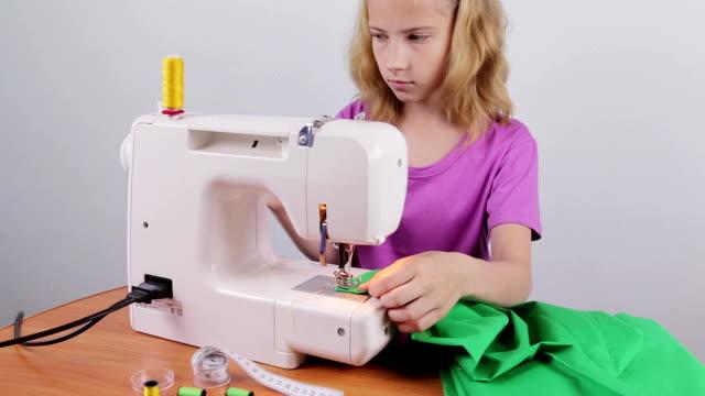 a teenage girl makes a string of thread - sarta video stock e b–roll