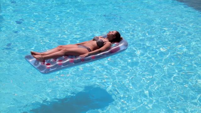 vidéos et rushes de adolescente sur radeau de piscine, poche tourné - allongé sur le dos
