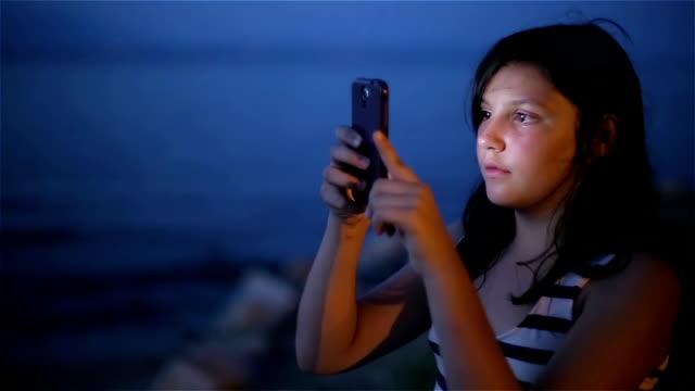 nastoletnia dziewczyna fotografująca morze w nocy za pomocą telefonu komórkowego - morze egejskie filmów i materiałów b-roll