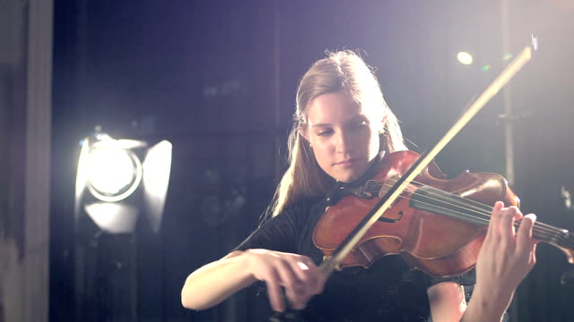Teenage girl playing violin in concert A 16 year old teenage girl playing the violin in a concert performance. classical concert stock videos & royalty-free footage