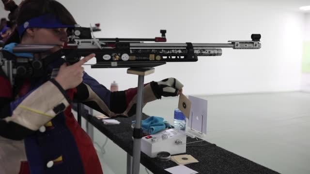 Teenage girl practicing air rifle shooting at shooting range