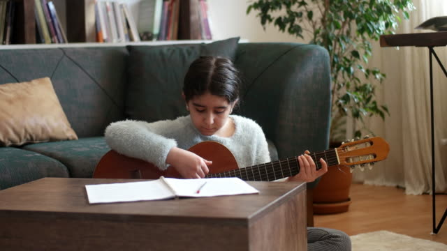 Teenage girl practicing guitar