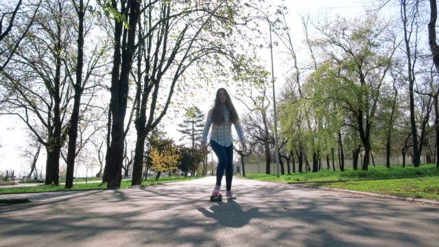 公園で短いスケートボードを練習十代の女の子、スローモーション - 春のファッション点の映像素材/bロール