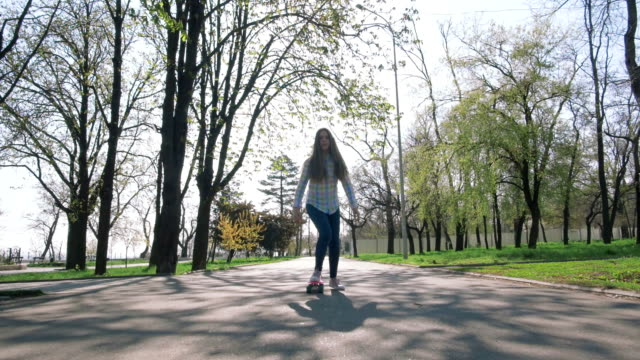 Teenage girl practicing short skateboard riding in park, slow motion ビデオ