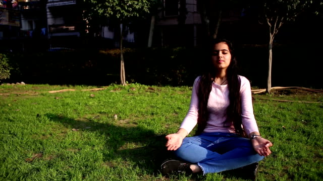 Teenage girl practicing yoga performing Gyan Mudra and lotus position outdoors with closed eyes. HD Video : Long hair teenage girl of Indian ethnicity sitting in the park and she doing meditation with closed eyes. Gyan Mudra is an influential Mudra (otherwise hand position) skillful for thousands of years by yogis which bring peace, quiet, plus religious progress. mental wellbeing stock videos & royalty-free footage