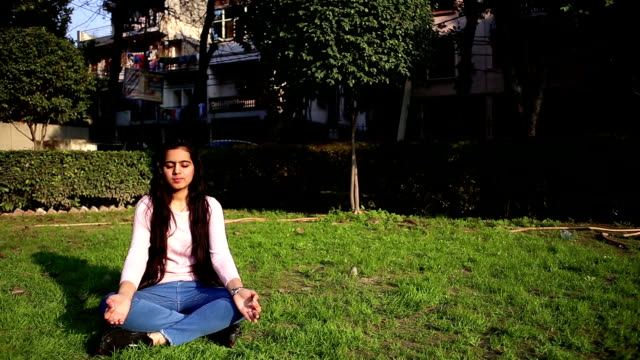 Teenage girl practicing yoga performing Gyan Mudra and lotus position outdoors with closed eyes. HD Video : Long hair teenage girl of Indian ethnicity sitting in the park and she doing meditation with closed eyes. Gyan Mudra is an influential Mudra (otherwise hand position) skillful for thousands of years by yogis which bring peace, quiet, plus religious progress. lotus position stock videos & royalty-free footage
