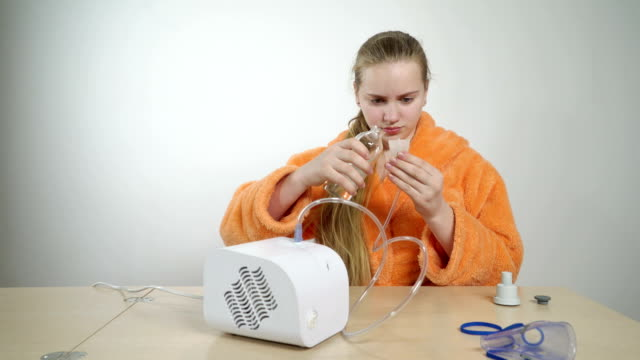 Teenage girl preparing to use a nebulizer for asthma treatment at home video
