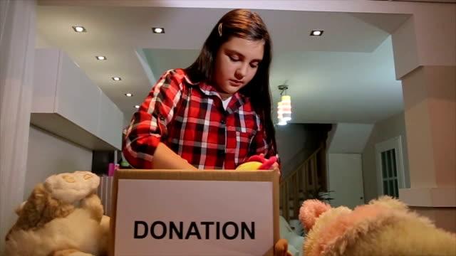 teenager-mädchen stellen spielzeug in spendenbox für andere kinder - kinderspielzeug stock-videos und b-roll-filmmaterial