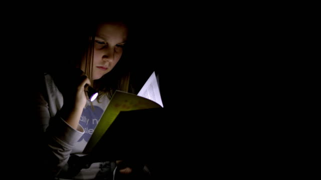 MS Teenage girl reading a book at night video