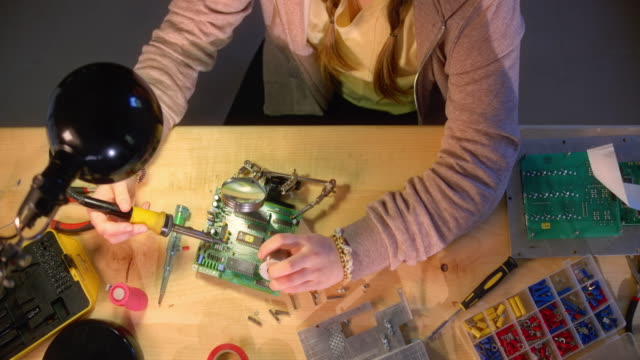 SLO MO LD Teenage girl repairing a motherboard with a soldering iron and wire Slow motion medium right above locked down shot of a teenage girl repairing a non functional motherboard by soldering it. Shot in Slovenia. table top view stock videos & royalty-free footage