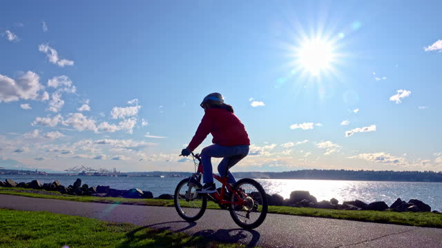 Teenage girl riding bike on Seattle waterfront trail with bright sun behind video