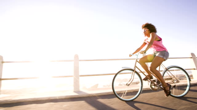 teenage girl riding su bicicleta cerca de la playa - vídeo