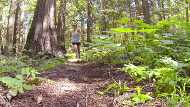 Teenage Girl running through forest with small pet dog video