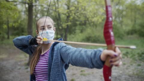 vídeos y material grabado en eventos de stock de adolescente disparando un arco en el bosque durante la pandemia covid-19 - actividades recreativas