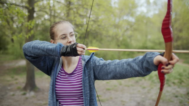 Teenage girl shooting a bow in the forest