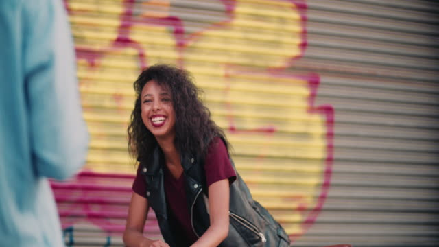 Teenage girl smiling at someone on a city street video