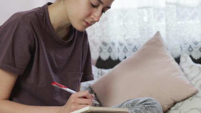 covid-19パンデミックの間に自宅で勉強している10代の少女 - 人里離れた点の映像素材/bロール