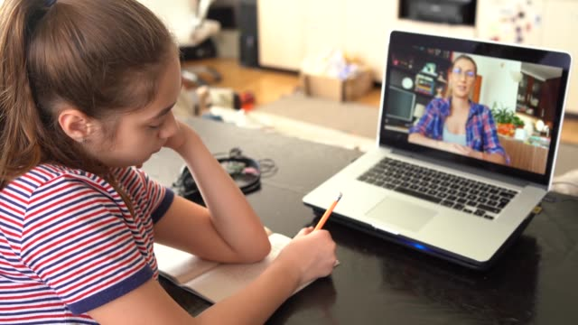 4k teenage girl studying with video online lesson at home   family in isolation - pokazywać filmów i materiałów b-roll