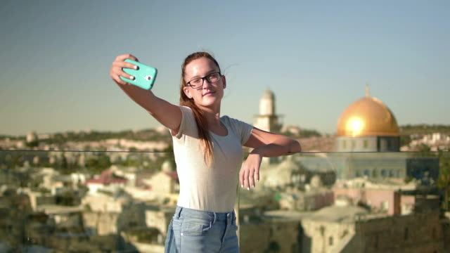 Teenage girl taking self ie in the background Dome of the Rock, Jerusalem, Israel video