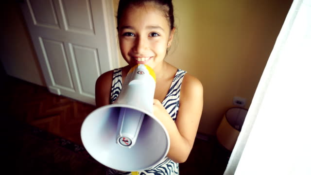 Teenage girl talking in megaphone Cute, teenage girl talking in megaphone and looking at camera. megaphone stock videos & royalty-free footage