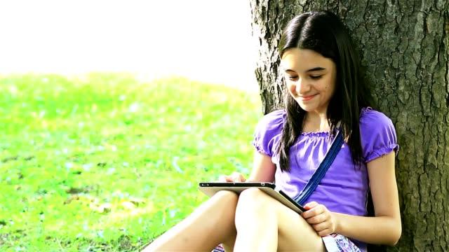 Teenage girl using digital tablet on grass video