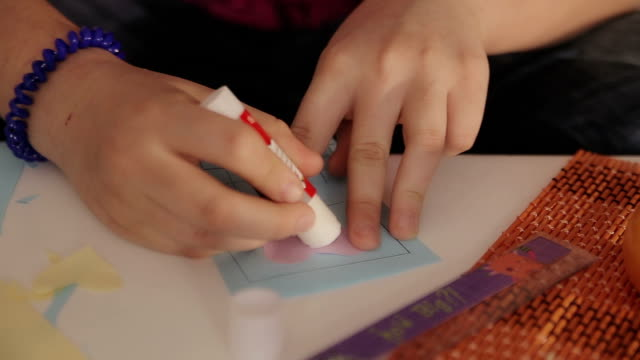 teenage girl using glue for paper,closeup video