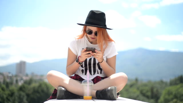 Teenage girl using smartphone on the roof video