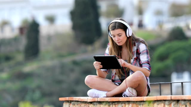 teenage girl watching and listening online content on a tablet - загружать стоковые видео и кадры b-roll