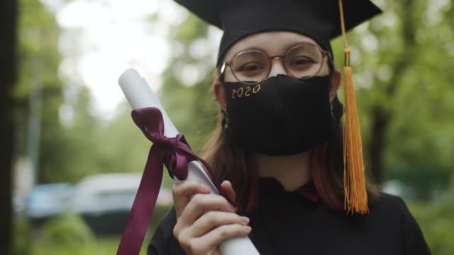 穿著畢業禮服、帽子和防護面具的少女 - 文憑 個影片檔及 b 捲影像