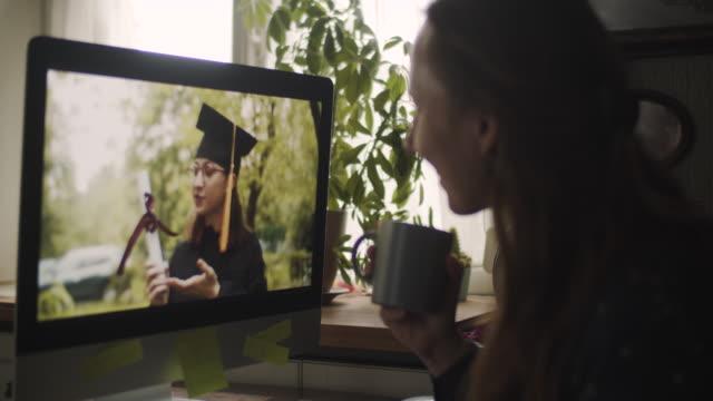 vídeos y material grabado en eventos de stock de adolescente que usa vestido de graduación y gorra saludando a su pariente o amigo en videollamada - graduación