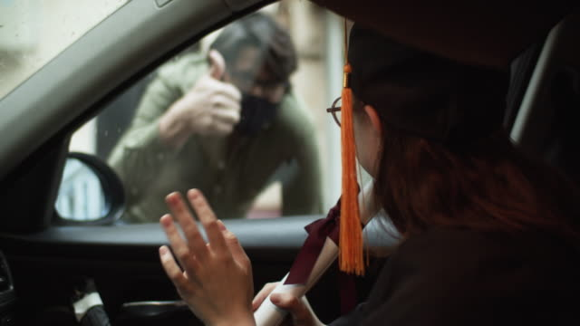 Teenage girl wearing graduation gown and cap with diploma in car and a men greeting her from a street Class of 2020 graduate in car during the COVID pandemic, shot using BMPCC 4k diploma stock videos & royalty-free footage