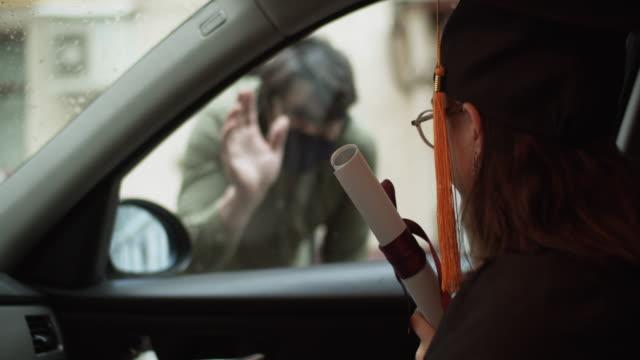 vidéos et rushes de adolescente utilisant la robe et la casquette de graduation avec le diplôme dans la voiture et un homme la saluant d'une rue - homme faire coucou voiture