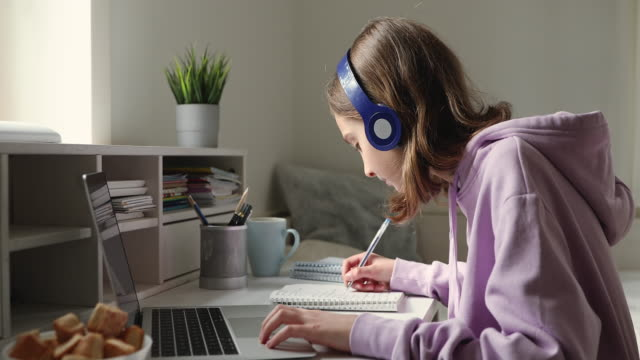 teenage girl wearing headphones studying online from home - didattica a distanza video stock e b–roll